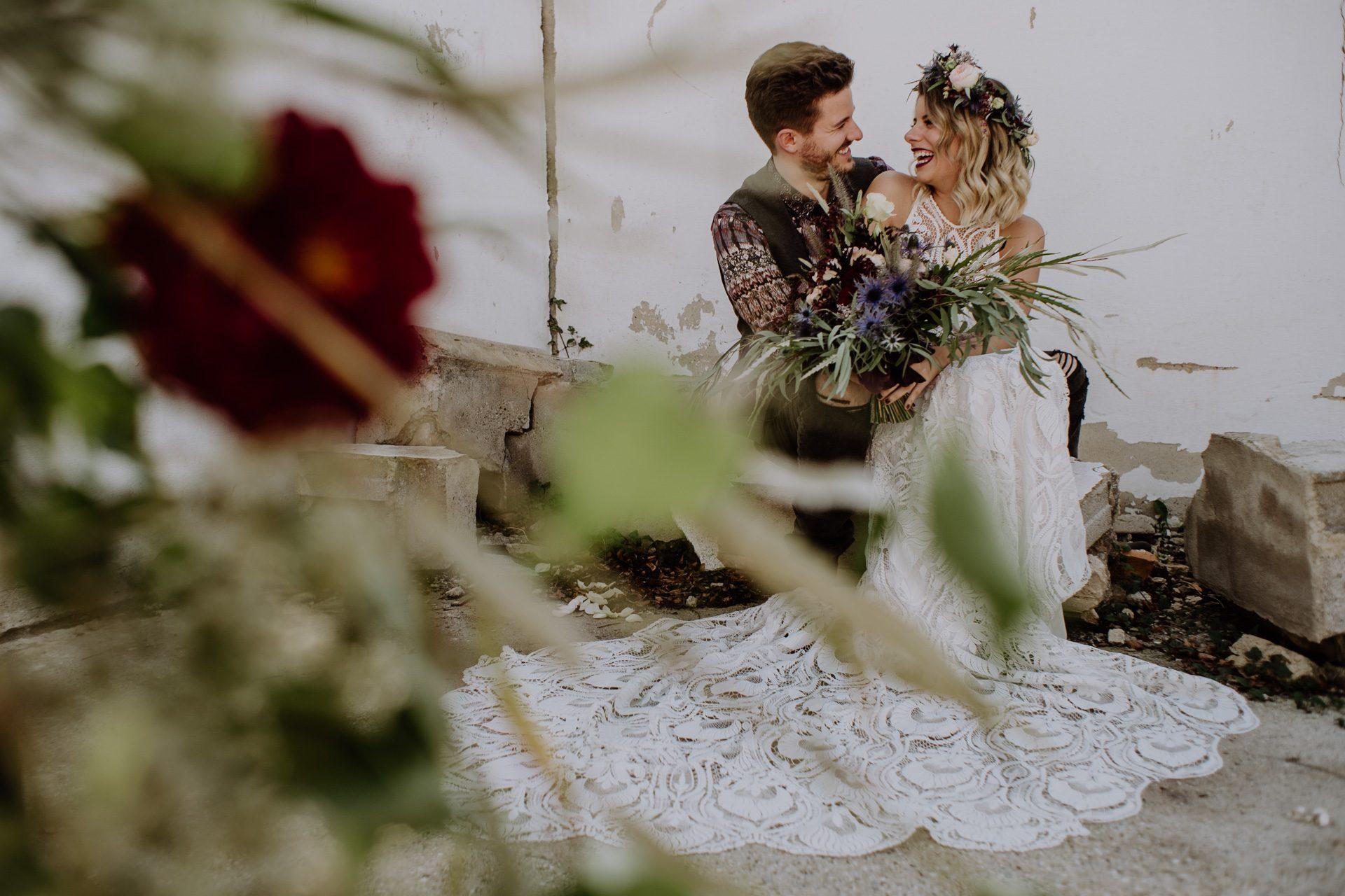 Braut mit wunderschönem Brautstrauß und Bräutigam lachen und sitzen auf einem Stein in einer alten Gärtnerei Hochzeit Hochzeitsideen Kamerakinder Weddings