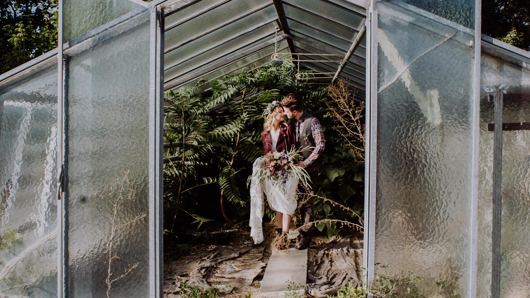 Braut und Bräutigam küssen sich in einem alten Glashaus Palmenhaus Hochzeit Kamerakinder Weddings