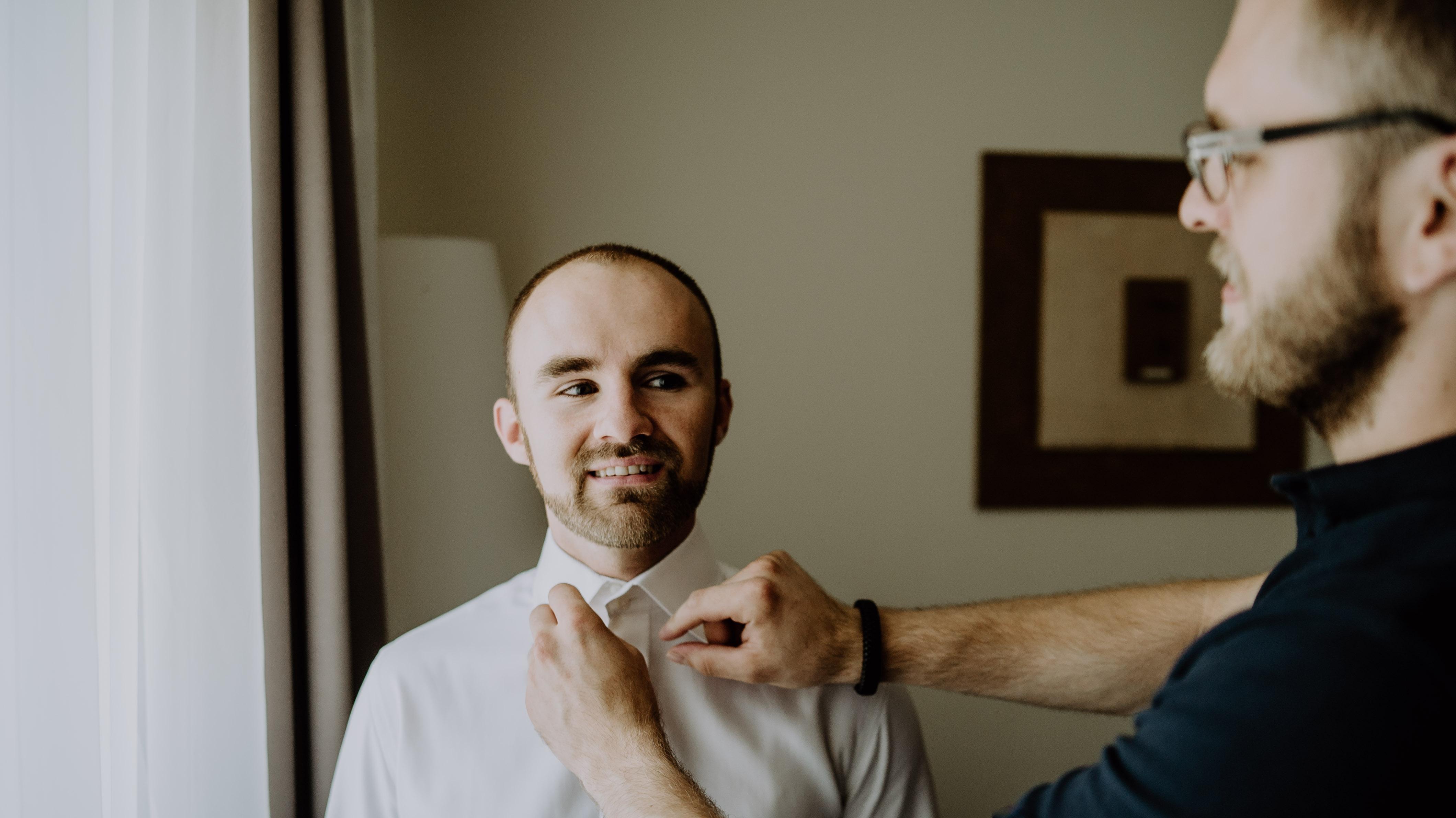 freie Trauung Bräutigam Getting Ready in einem Hotel Trauzeuge richtet Fliege Hochzeit Kamerakinder Weddings