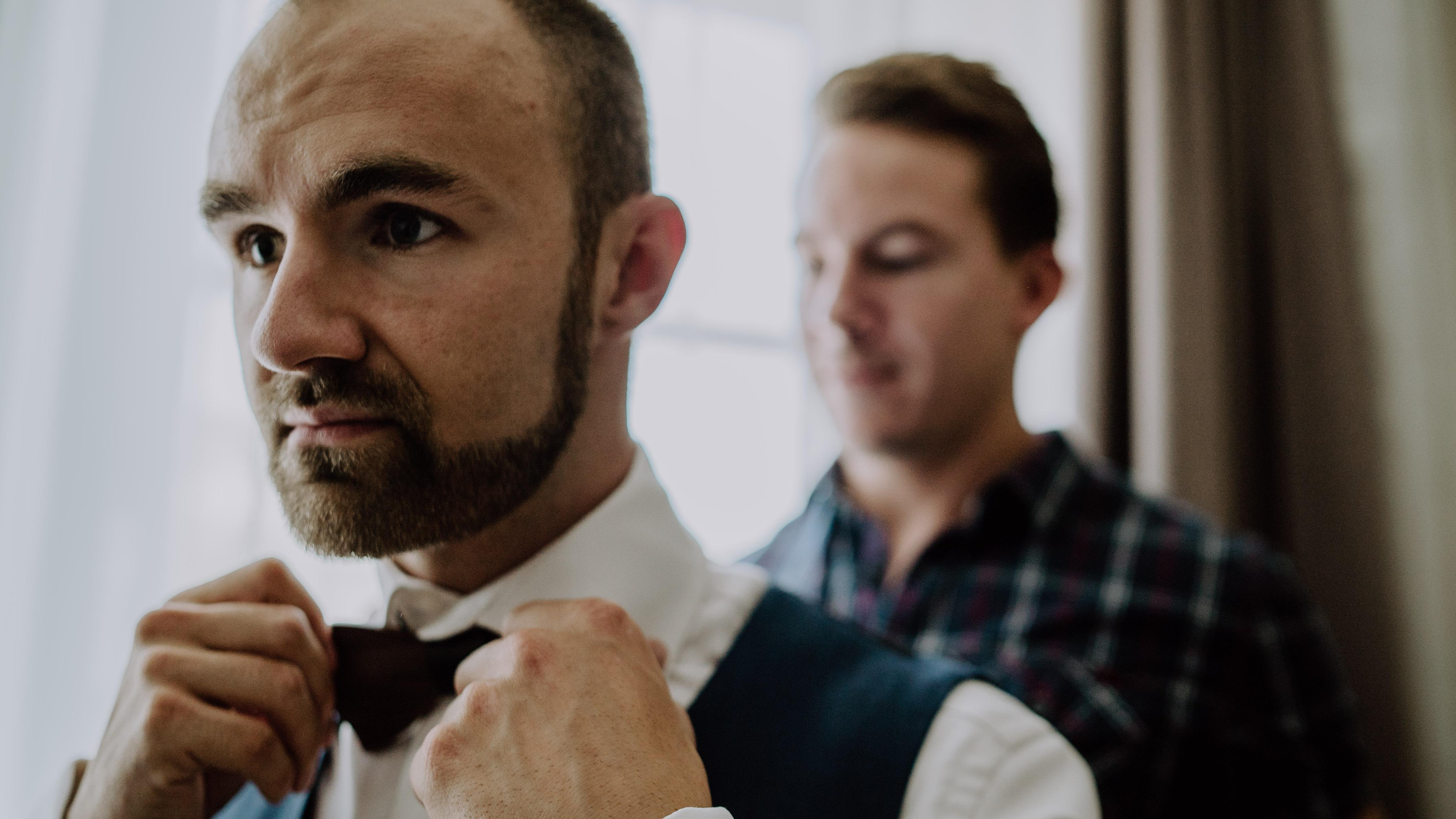 Bräutigam Getting Ready richtet sich Fliege Trauzeuge im Hintergrund Hotel Hochzeit Kamerakinder Weddings