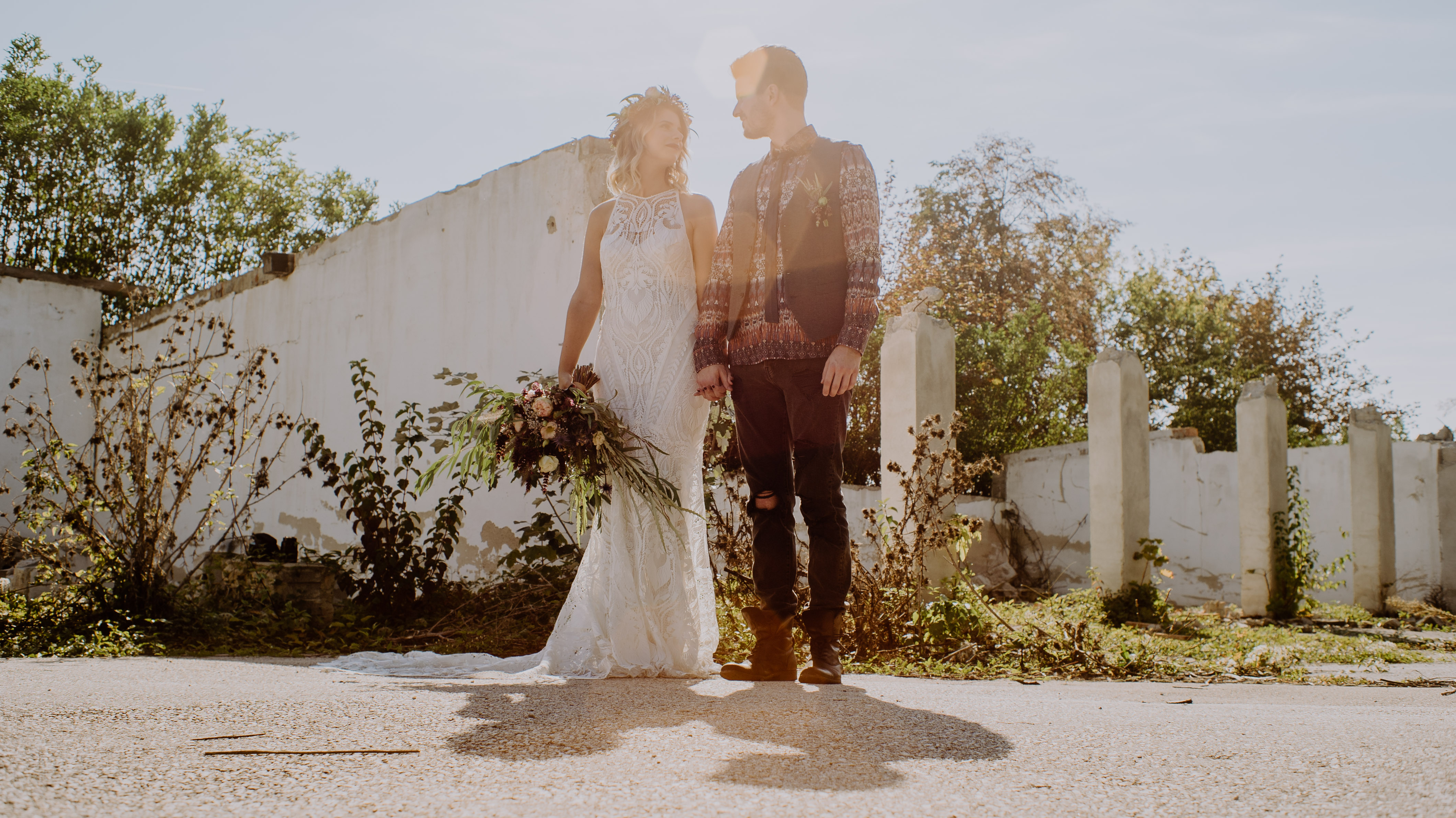 Brautpaar steht im Sonnenuntergang in einer alten Gärtnerei Hochzeit Kamerakinder Weddings