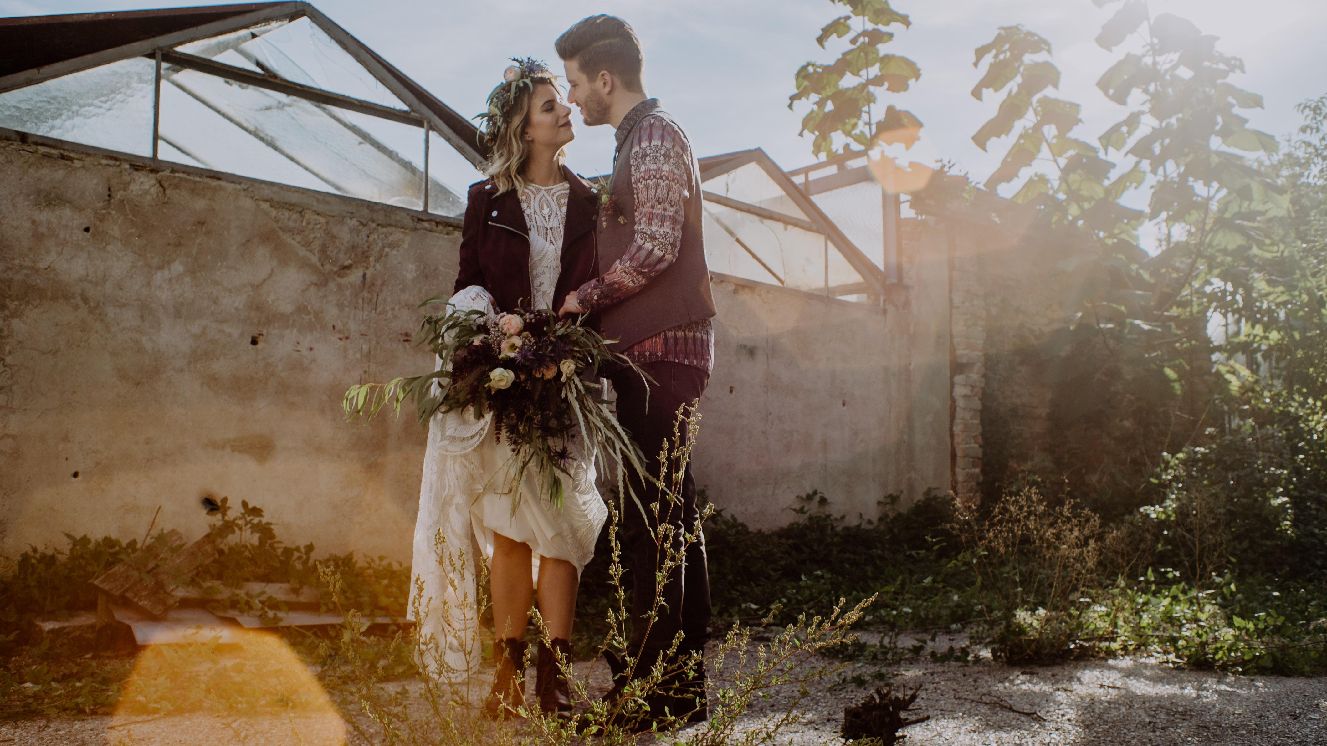Brautpaar küsst sich in einem alten Industriegelände Braut mit Lederjacke großer Blumenstrauß Hochzeit Kamerakinder Weddings