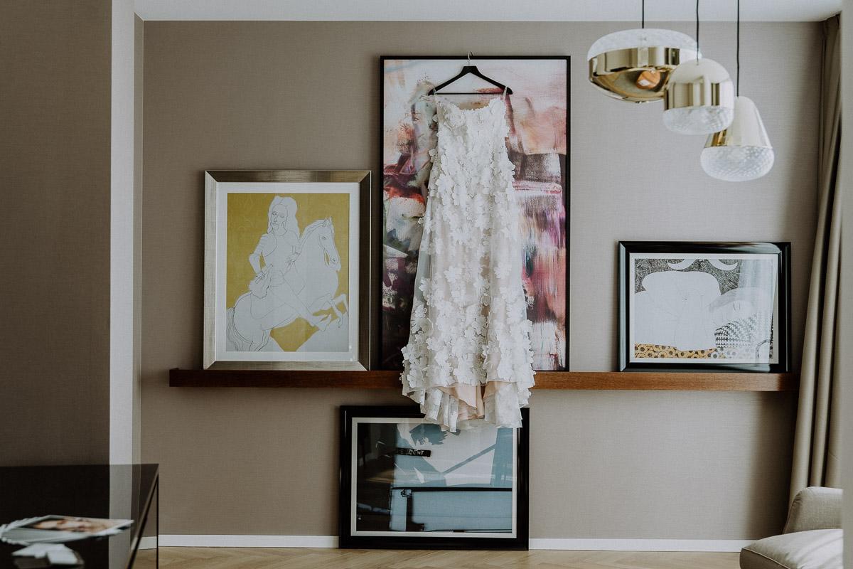 ein Brautkleid hängt im Andaz Vienna Hotelzimmer während Getting Ready der Braut by Kamerakinder Weddings