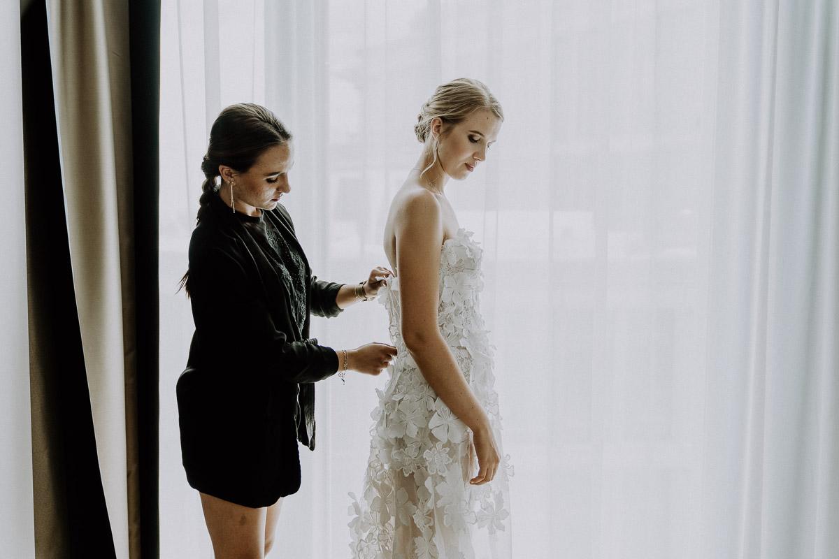 Trauzeugin hilft der Braut beim Brautkleid anziehen im Andaz Vienna Hotelzimmer beim Getting Ready für die Hochzeit by Kamerakinder Weddings