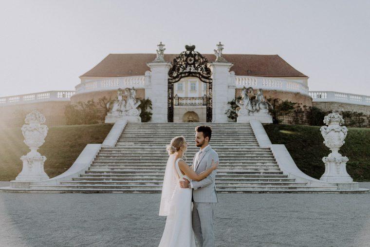 Brautpaar steht vor Schloss Hof und umarmt sich beim Sonnenuntergang After-Wedding-Shooting