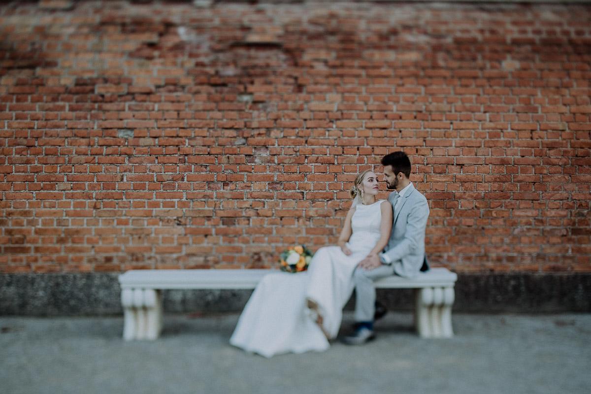 Brautpaar sitzt auf Steinbank in Schloss Hof und schaut sich verliebt an beim After-Wedding-Shooting in Niederösterreich