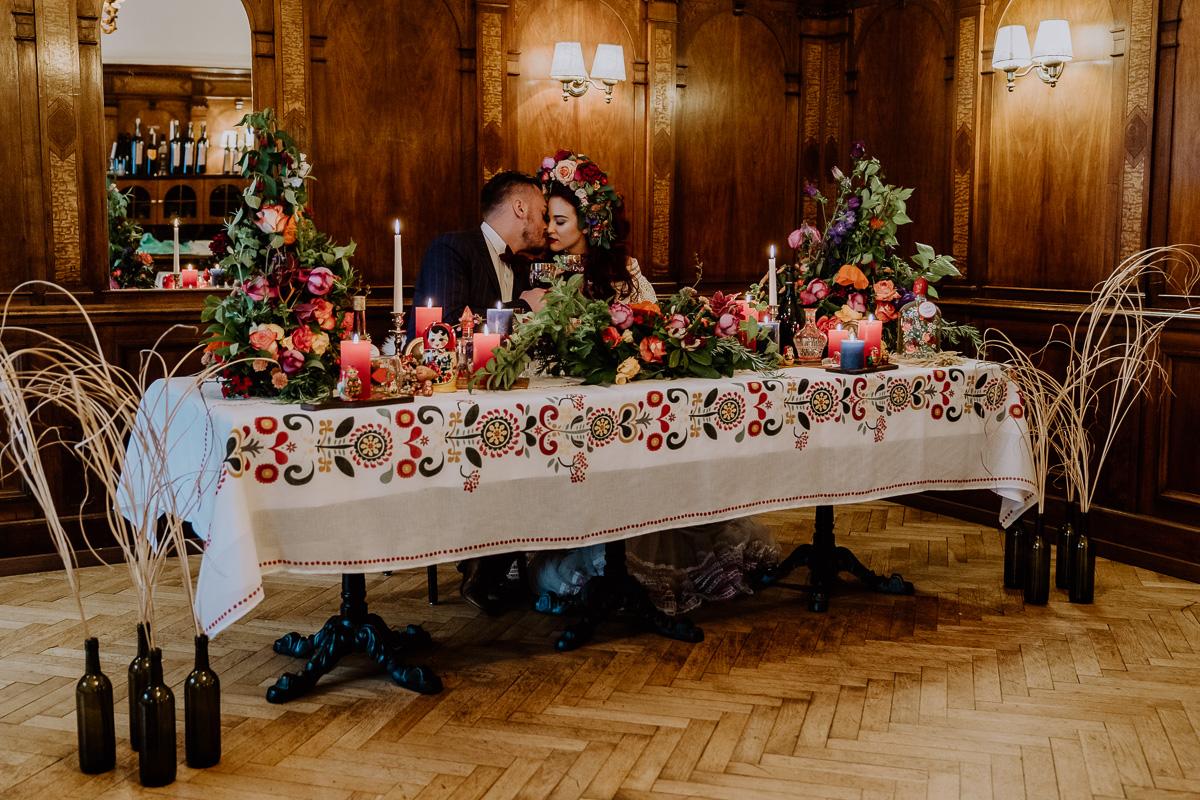 Hochzeitsinspiration Brautpaar sitzt am Brauttisch mit vielen Kerzen, viel bunter Dekoration und bohemian Flair und ganz viel Blumenschmuck boho Tischdekoration
